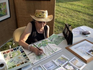 Polly Meltzer at work on watercolor painting of river flora and sun turtle.
