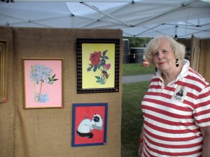 Framingham Artist Guild Member Merrillee Torres poses with some of her latest works, August 12, 2011