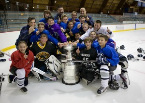 Framingham Youth Hockey Peewee ''A'' Team with coaches Phil Idelson (left), Joe MacIness (center, back), and Charlie Stefanini (right), were lucky enough to be on the ice when the cup arrived at Loring Arena.
