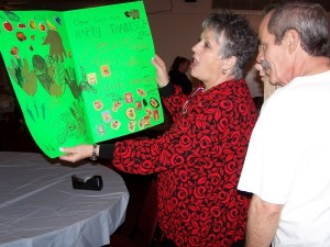 Karen & Mark Curtis looking over a ''Thank You'' card made by Framingham Girls Scouts.